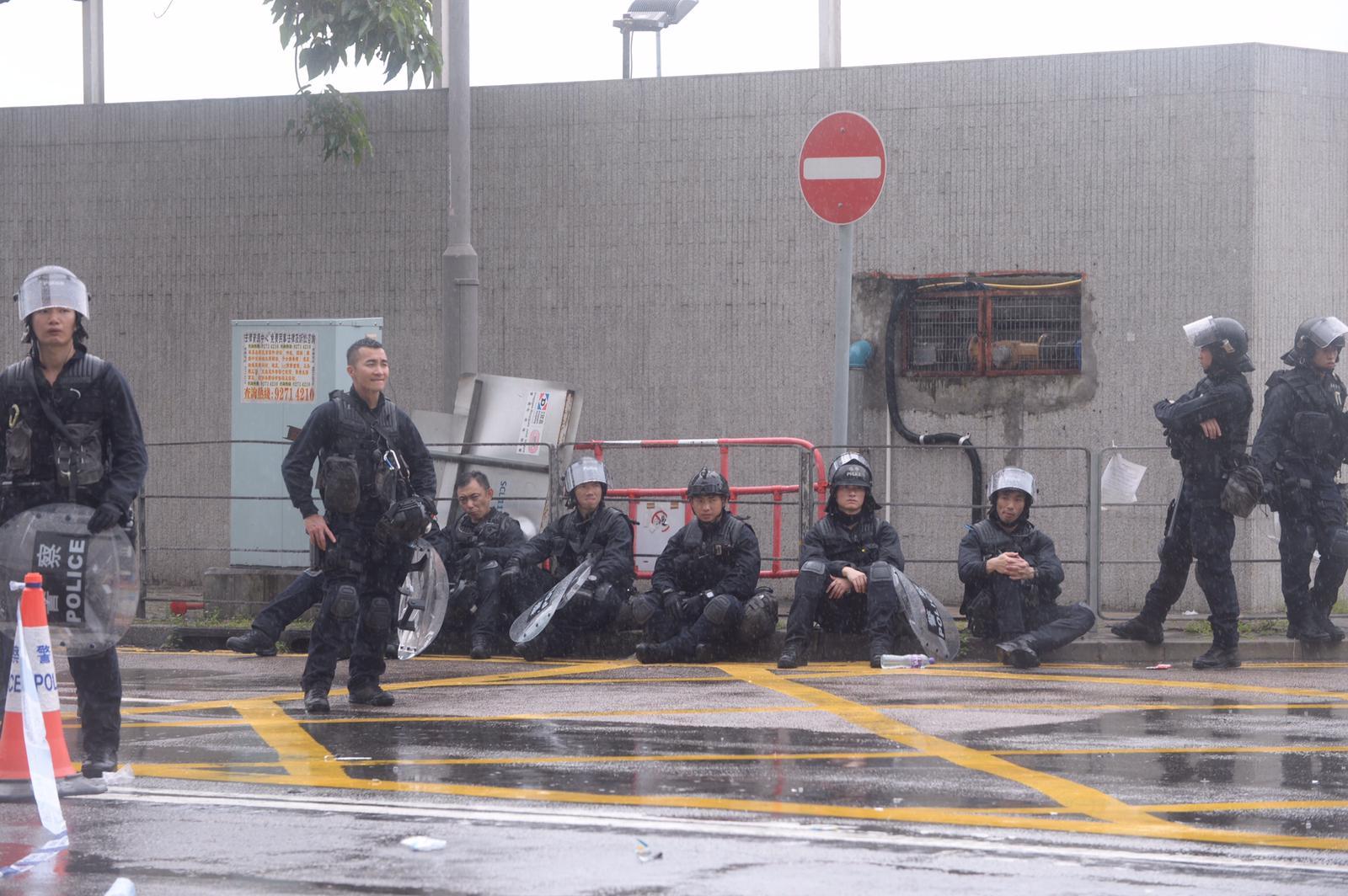 部分警員累倒,坐在地上休息。