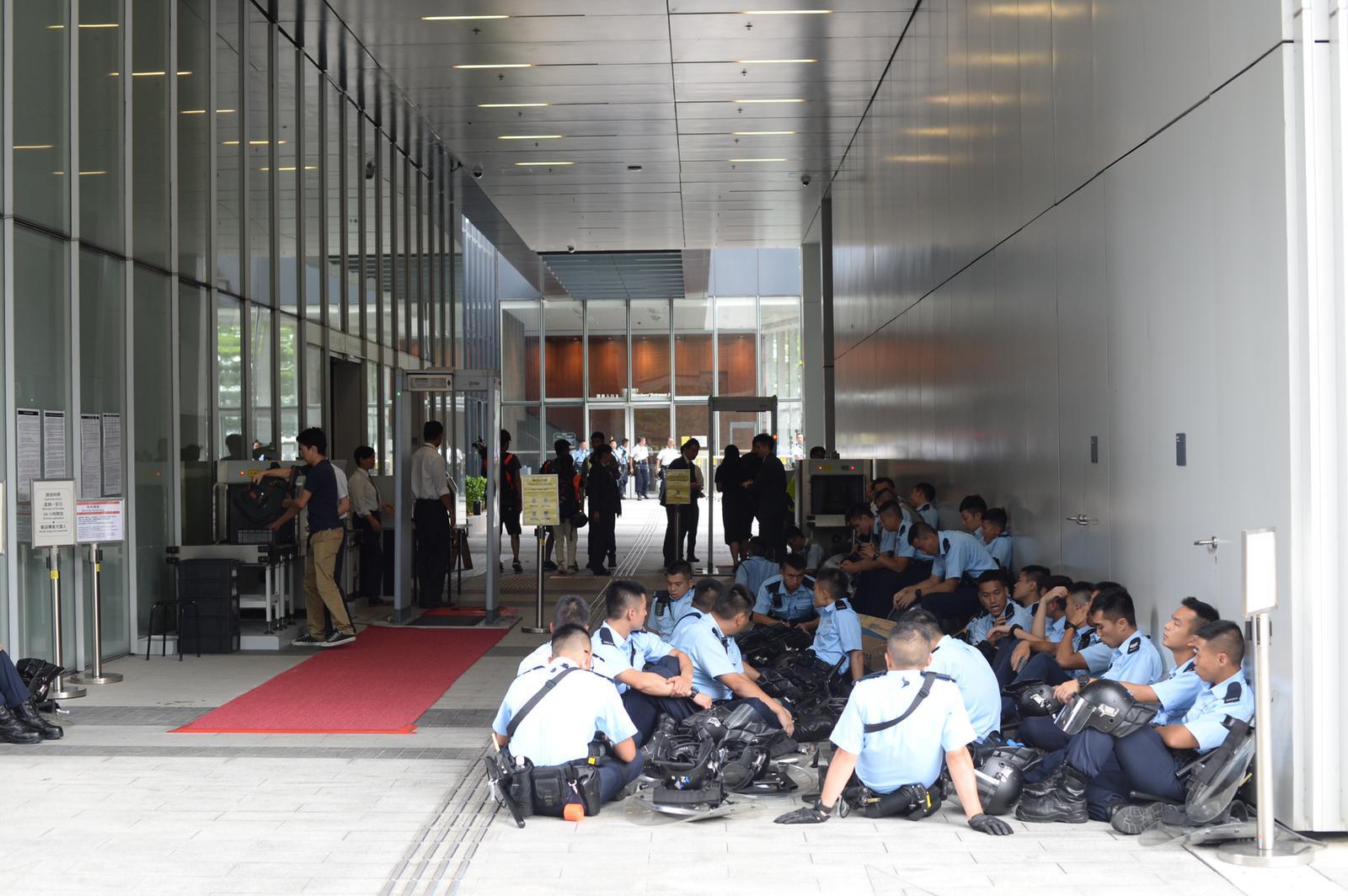 部分警員徹夜留守後疲憊不堪,坐在地上休息。