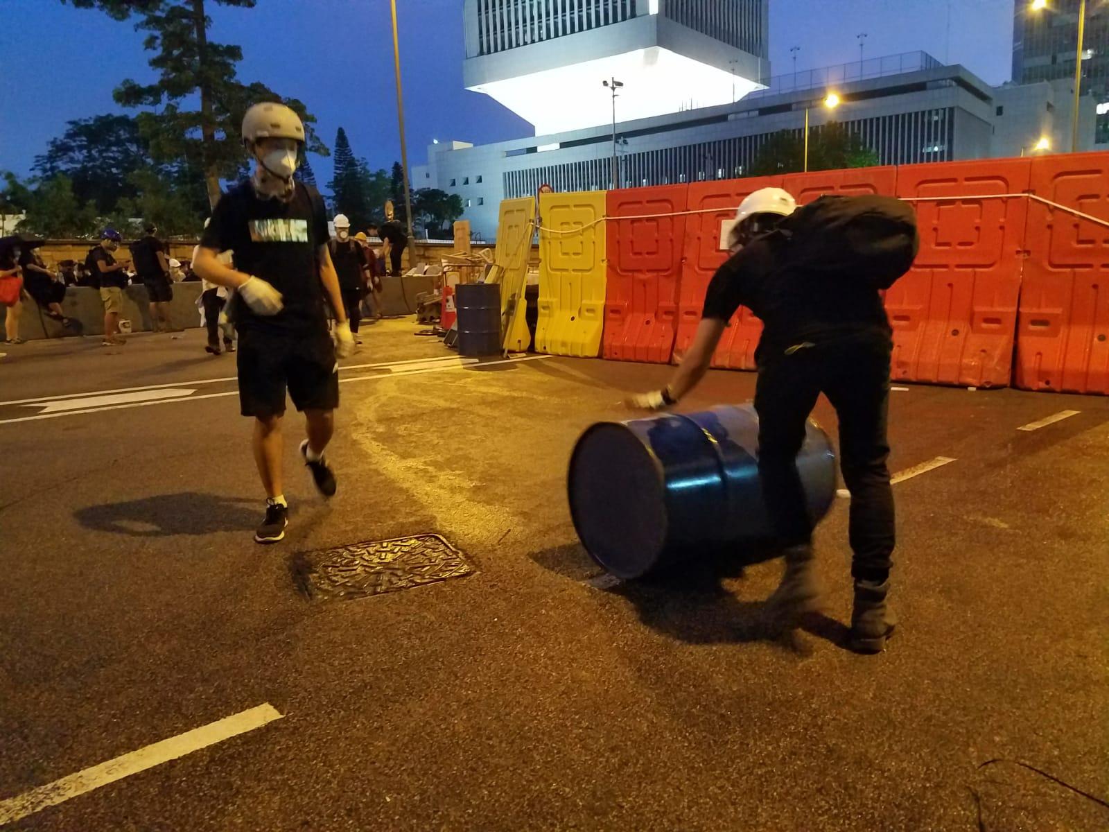 有示威者從佔領區附近一個地盤搬出大量金屬和泥頭。