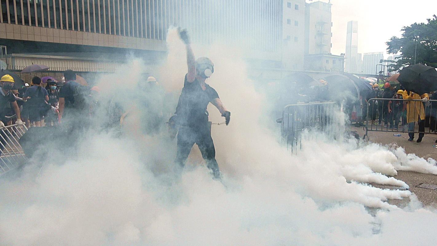 有示威者執起地上的手擲催淚彈掟回。