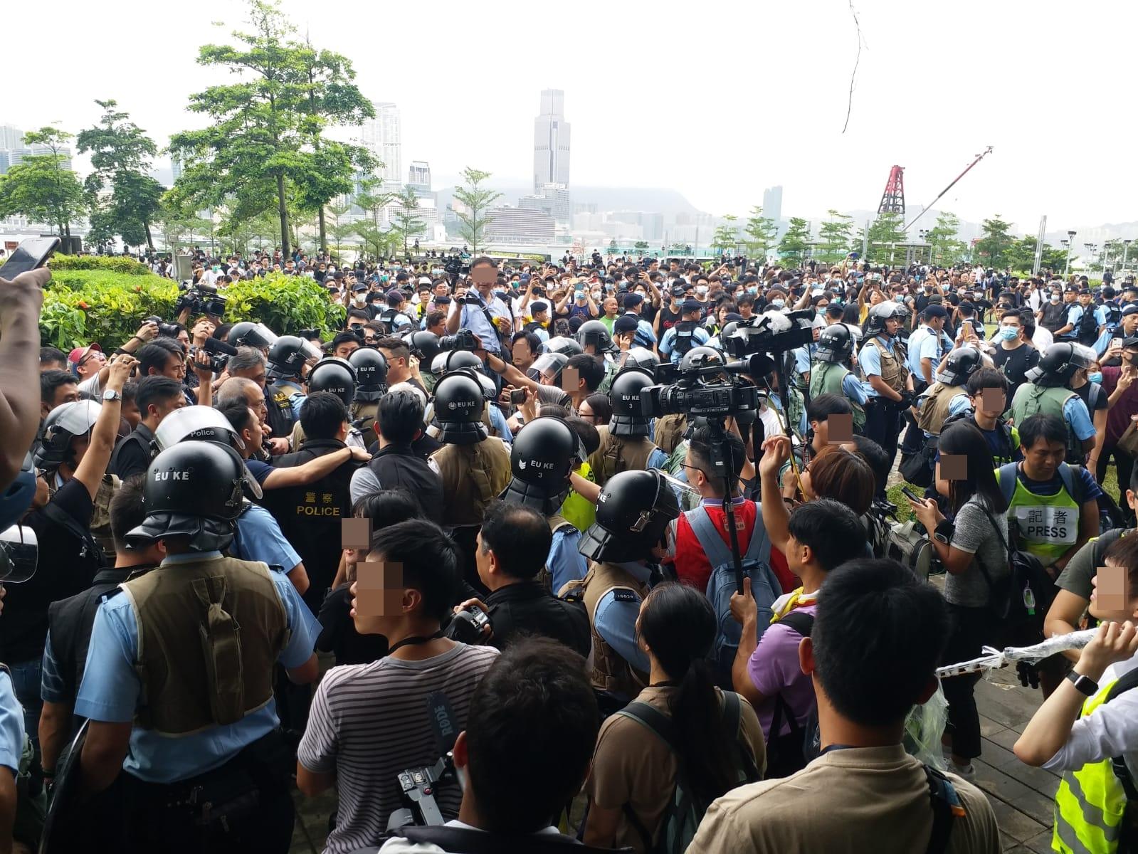 添馬公園有警察要求向一名男士搜身,隨即被在場人士圍繞。