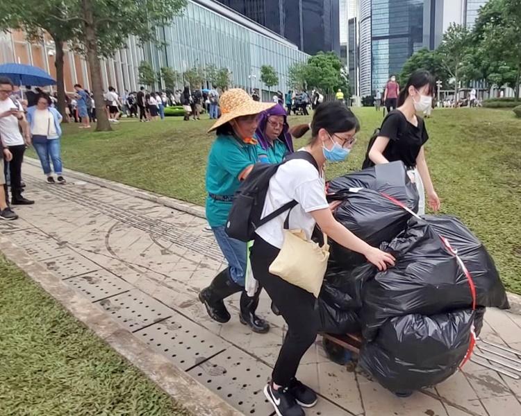 有市民幫忙清潔工人推垃圾車。