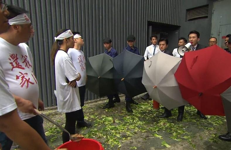 接龍保安打開雨傘,造成「雨傘陣」為大龍生護駕。影片截圖