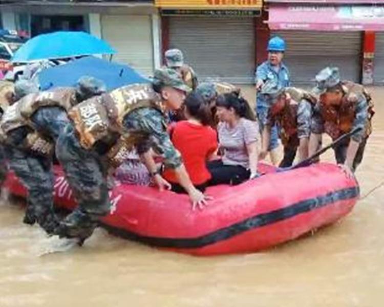 救援人员用橡皮艇将被困居民救出。网图