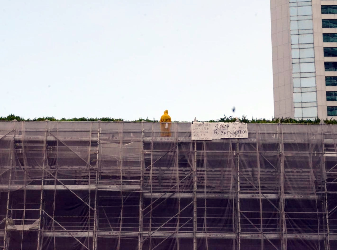 男子在金鐘太古廣場的平台掛上反對修例的橫額。