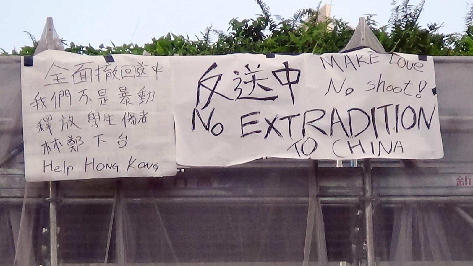 一名男子在金鐘太古廣場的平台掛上反對修例的橫額。