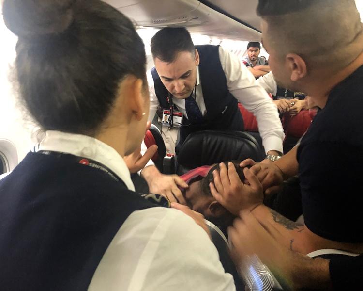 乘客合力捉住他。AP