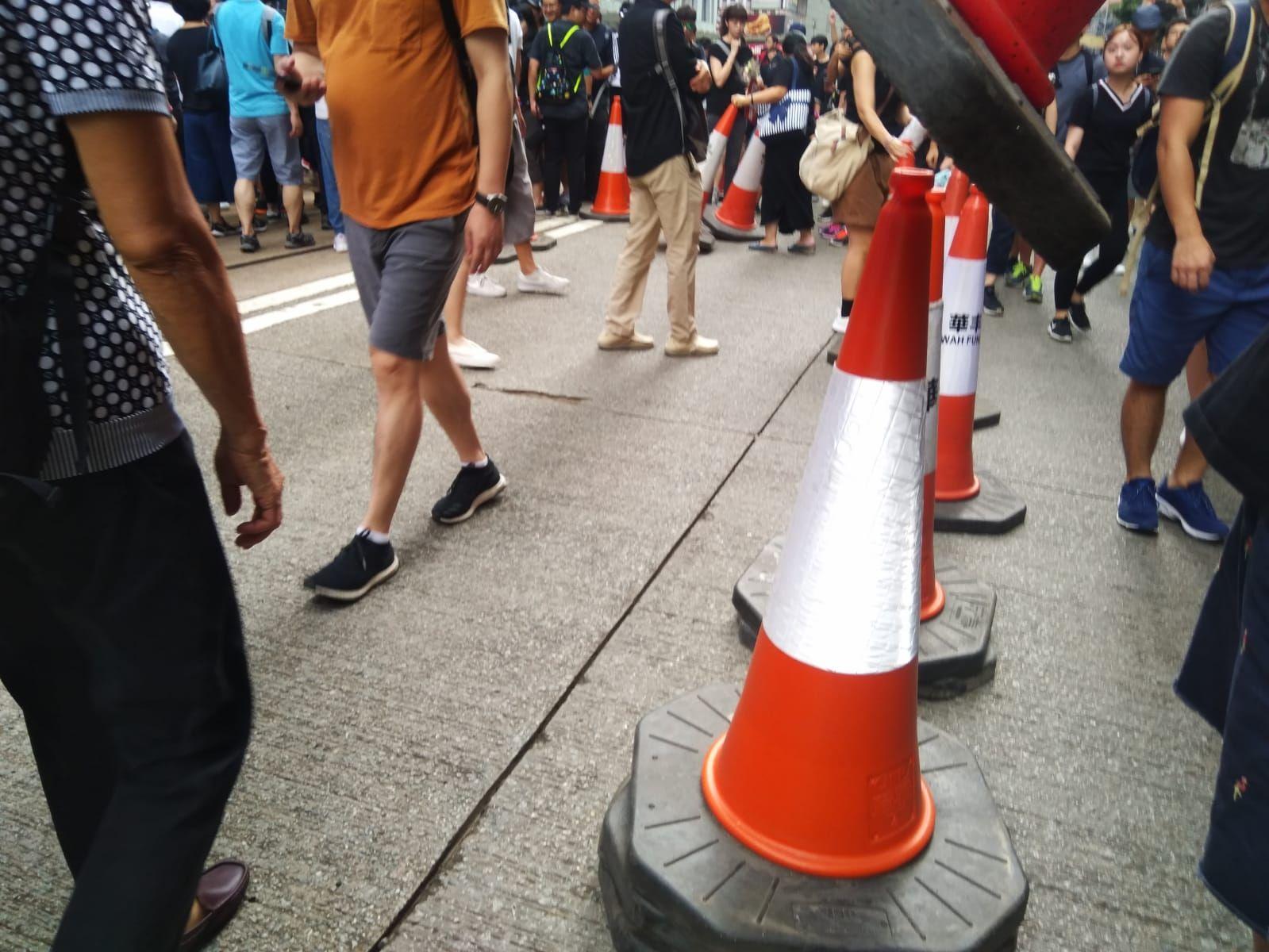 由於相反方向的遊行重疊,有市民將置於電車路旁的雪糕筒移開開路。