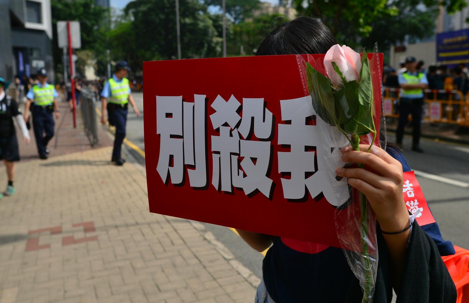 遊行人士舉出標語要求警方促停止使用武力。