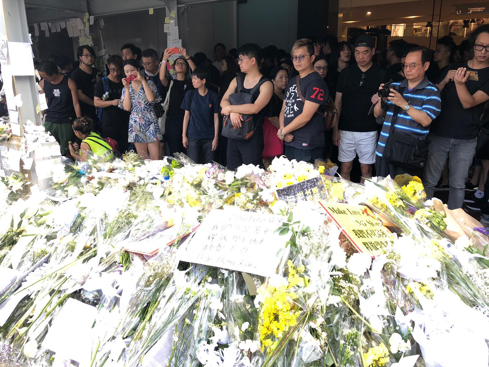 遊行人士在太古廣場外獻花悼念墮地身亡的示威者