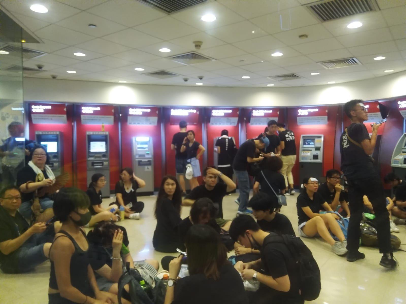 有市民在有冷氣的銀行櫃員機中心休息。