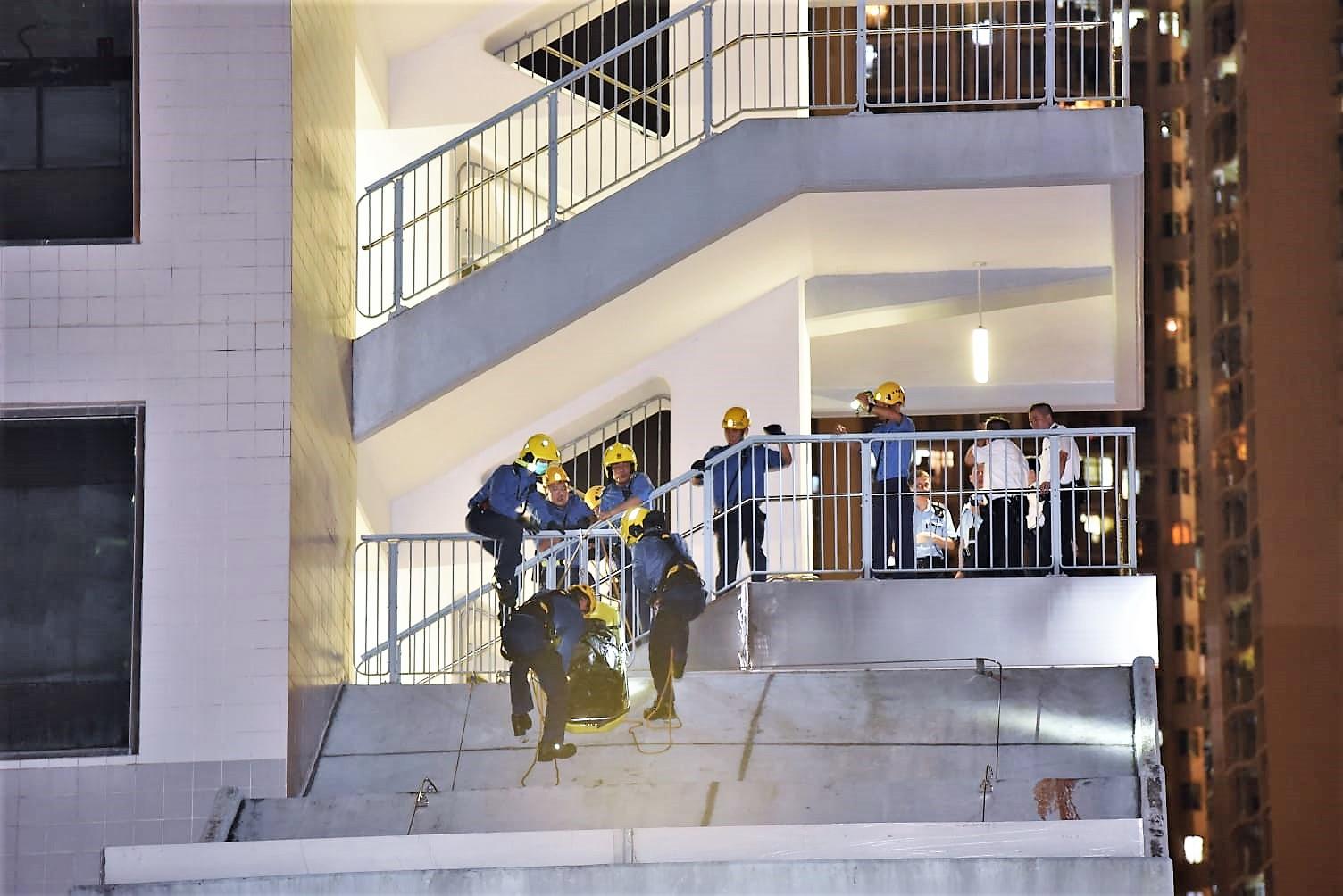 消防員協助將死者抬回梯間。