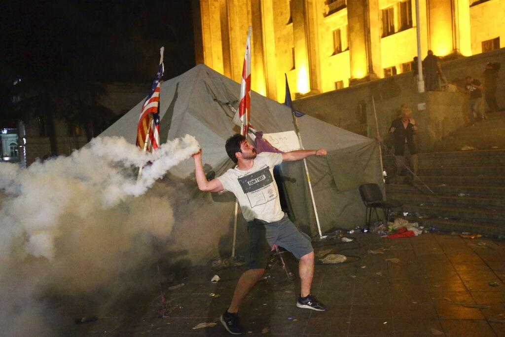 示威者向警察还击催泪弹。图片