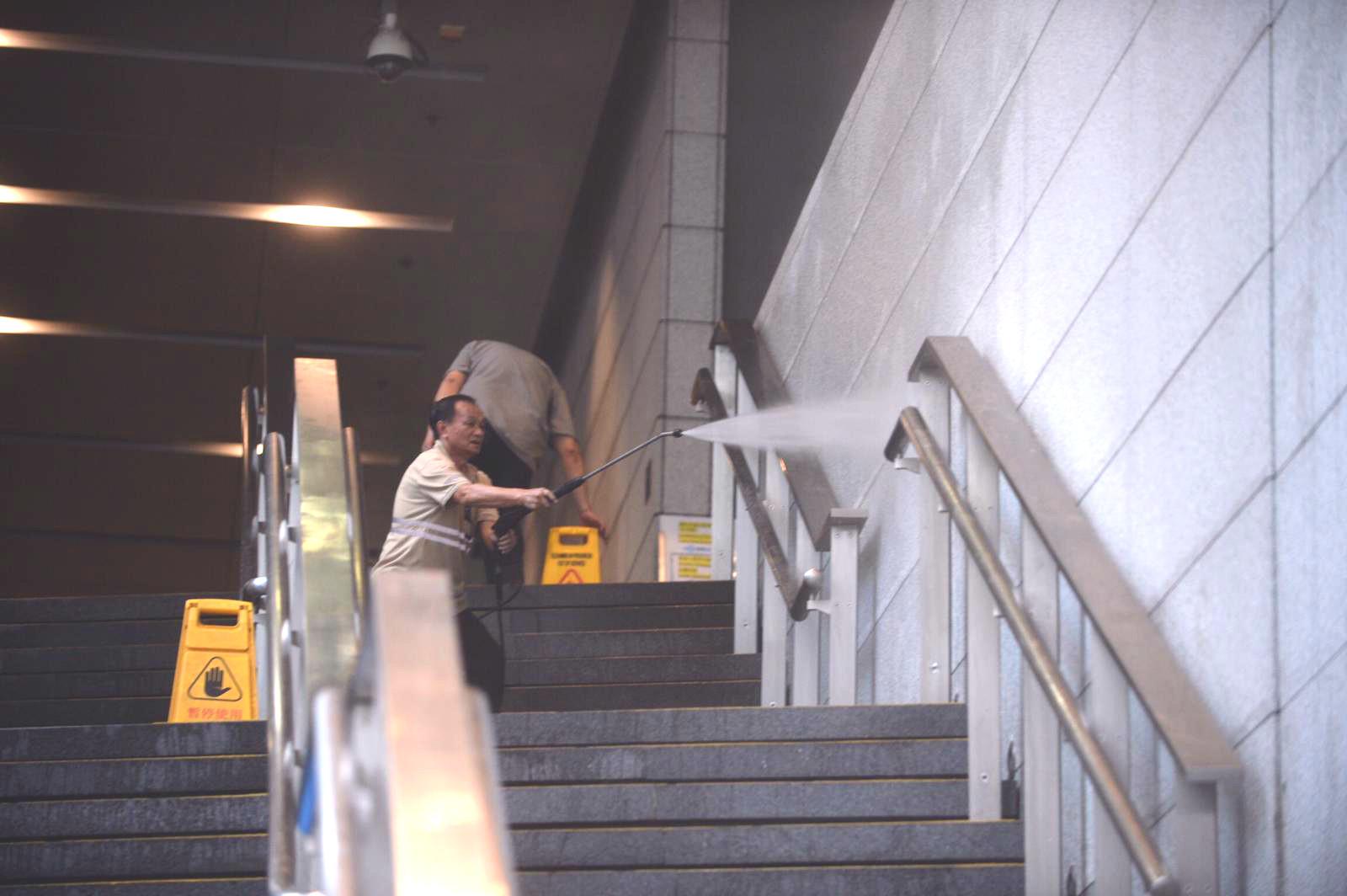 清潔工繼續清洗灣仔警察總部外牆行人路。