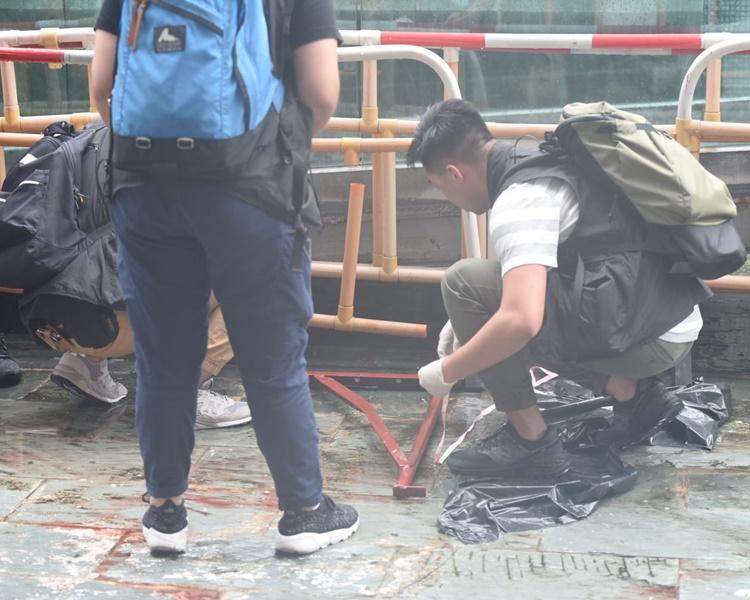 警員檢起墮下擊斃女途人的鐵架。