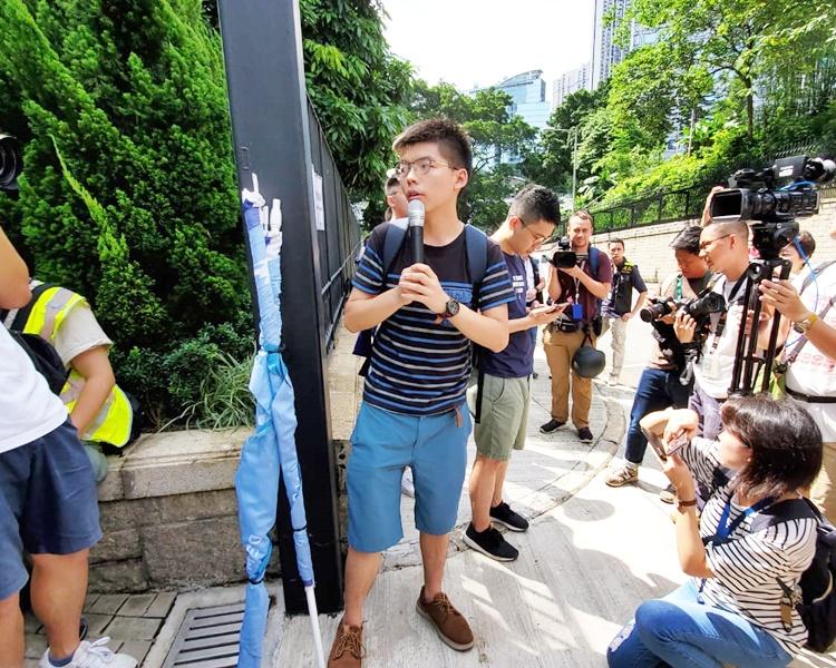 黃之鋒(中)響應網上呼籲到場示威。