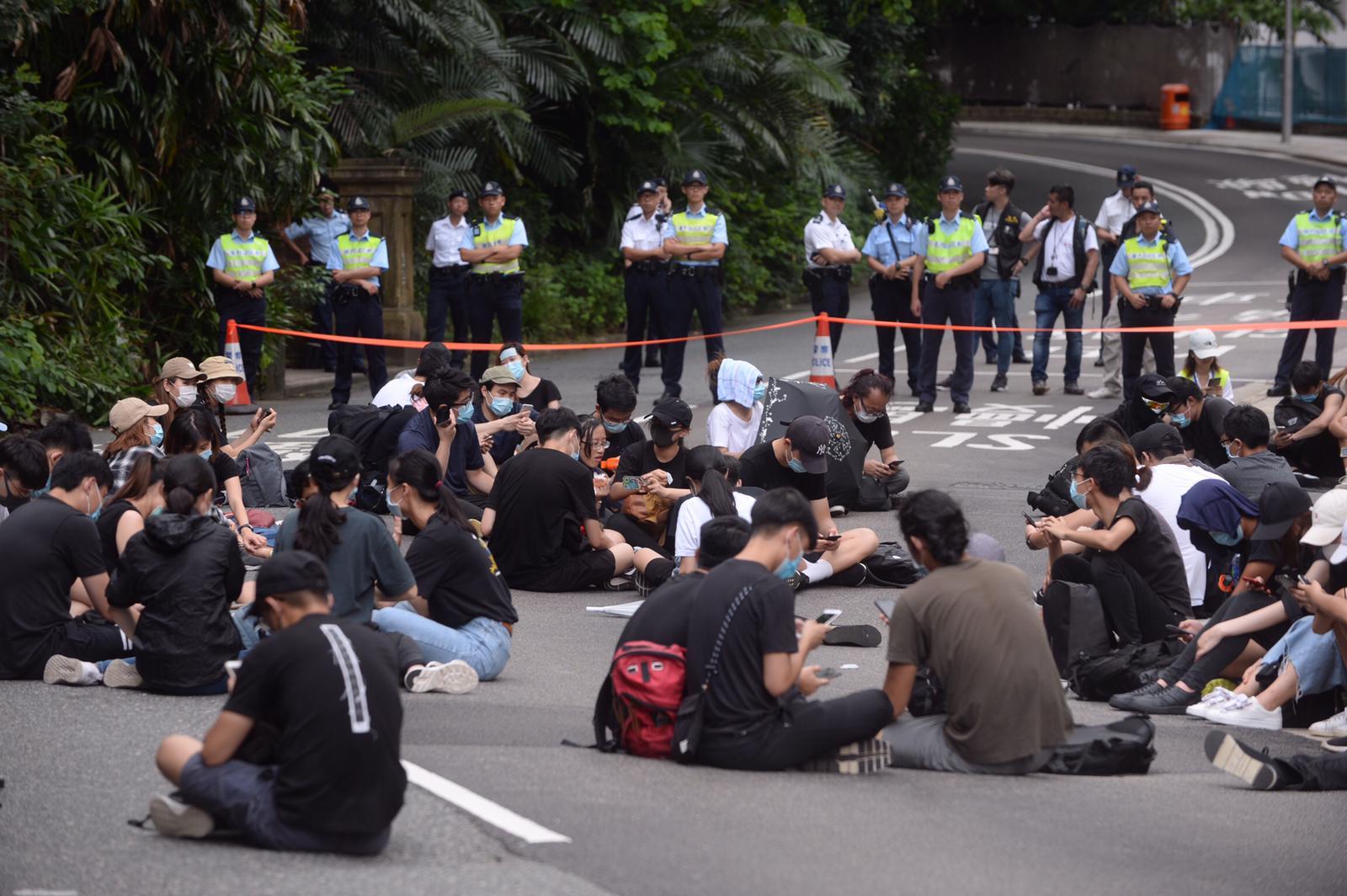 仍有逾百名示威者聚集,他們席地而坐。