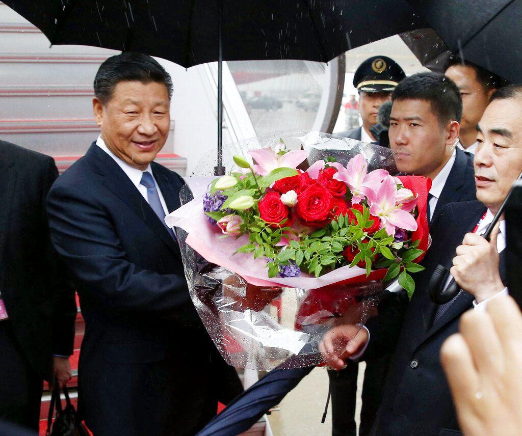 現場人員向習近平送上鮮花。AP