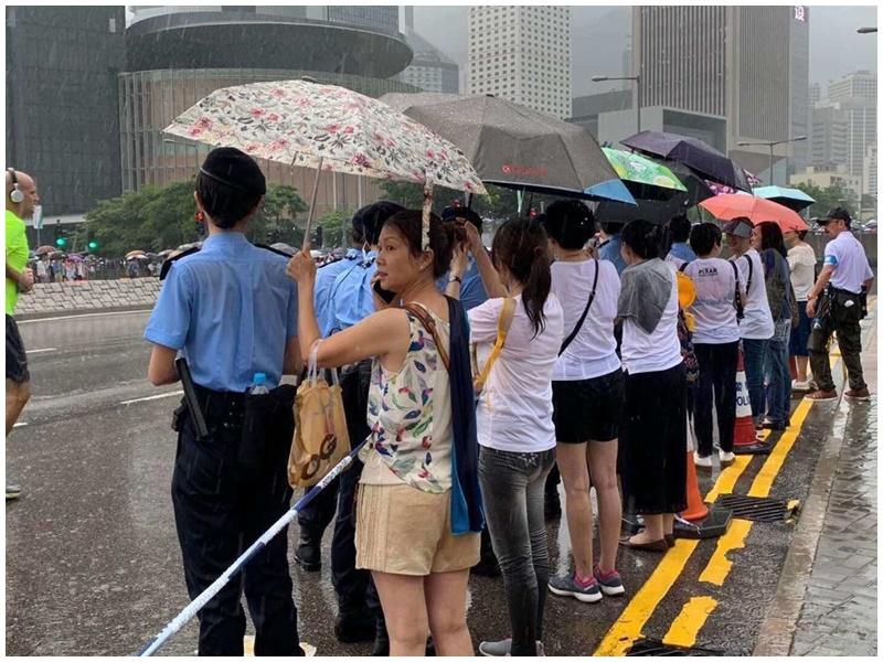 市民為警撐傘。