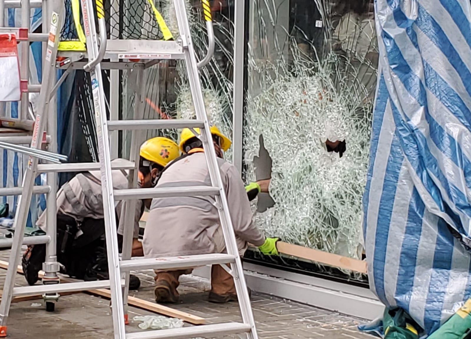 數名工人正在維修被毀壞的玻璃外牆。