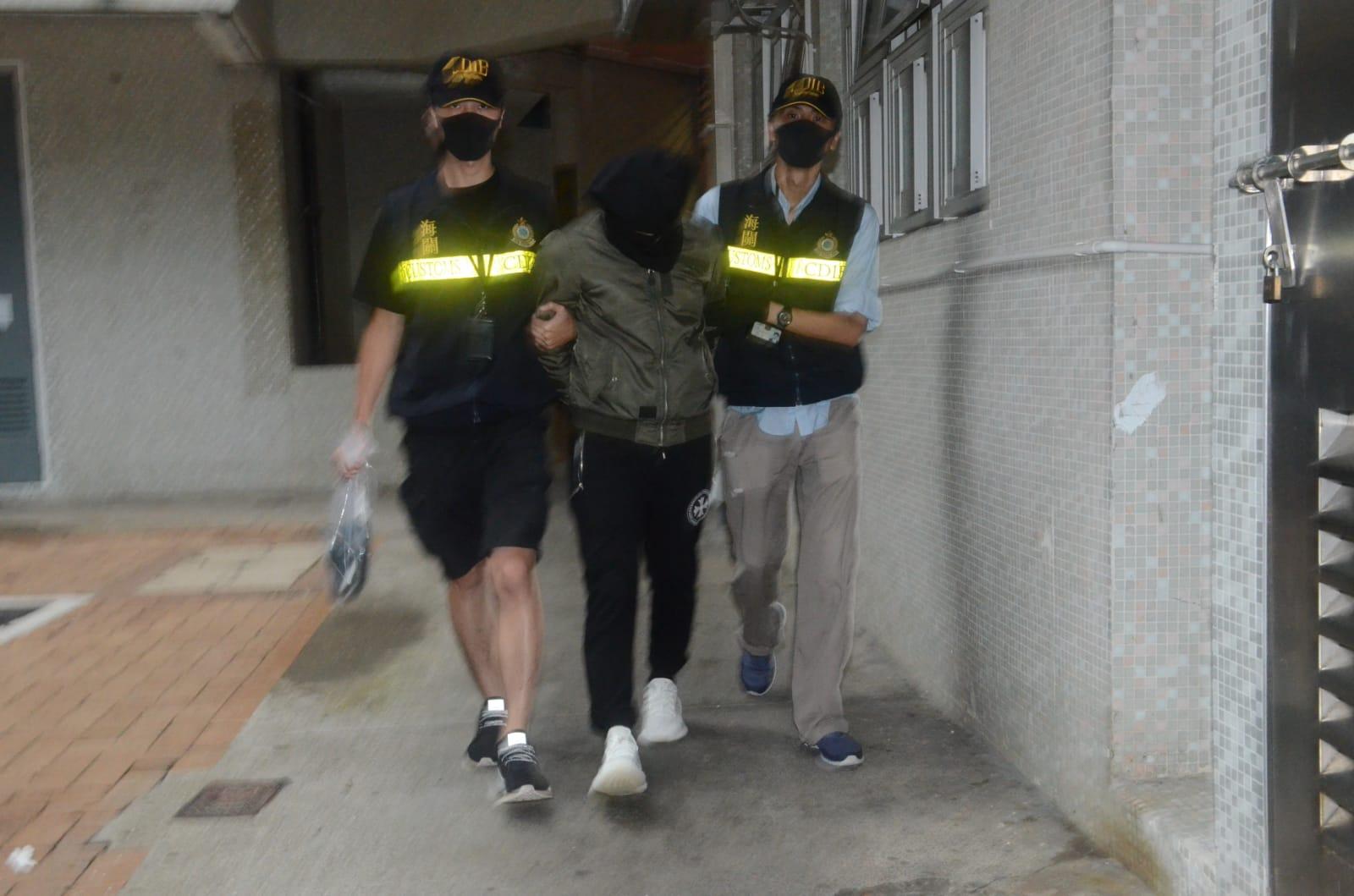 疑犯(中)被押返慈雲山慈樂邨樂旺樓一單位再作進一步搜查。