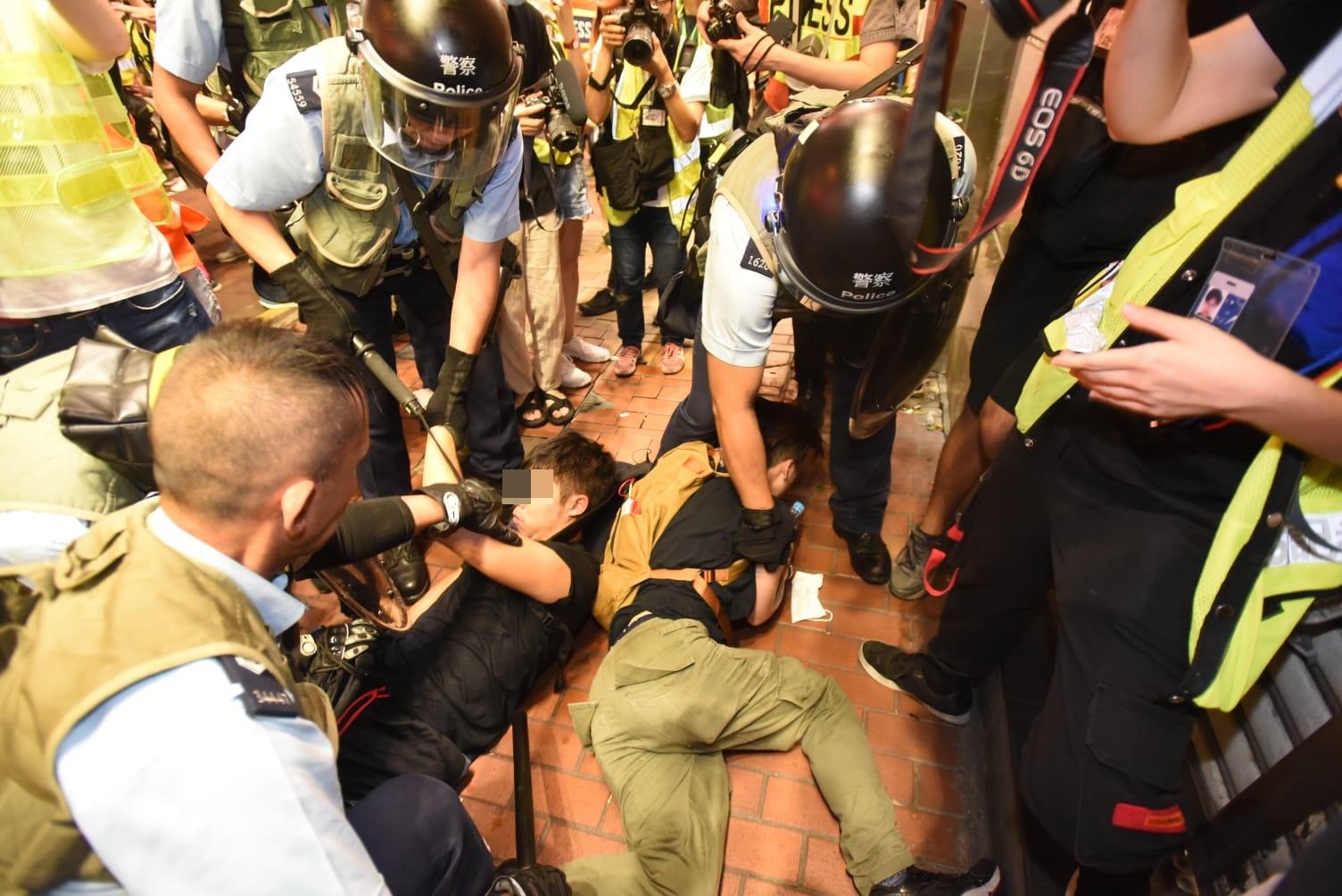 有示威者被按在地上。