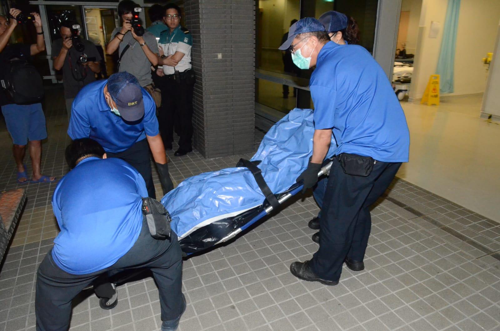 食環署工人晚上將遺體運送殮房。