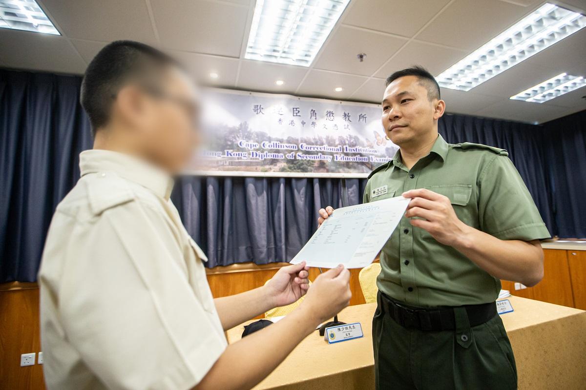 歌連臣角懲教所監督陳少恒(右)頒發成績通知書予青少年在囚人士。政府新聞處