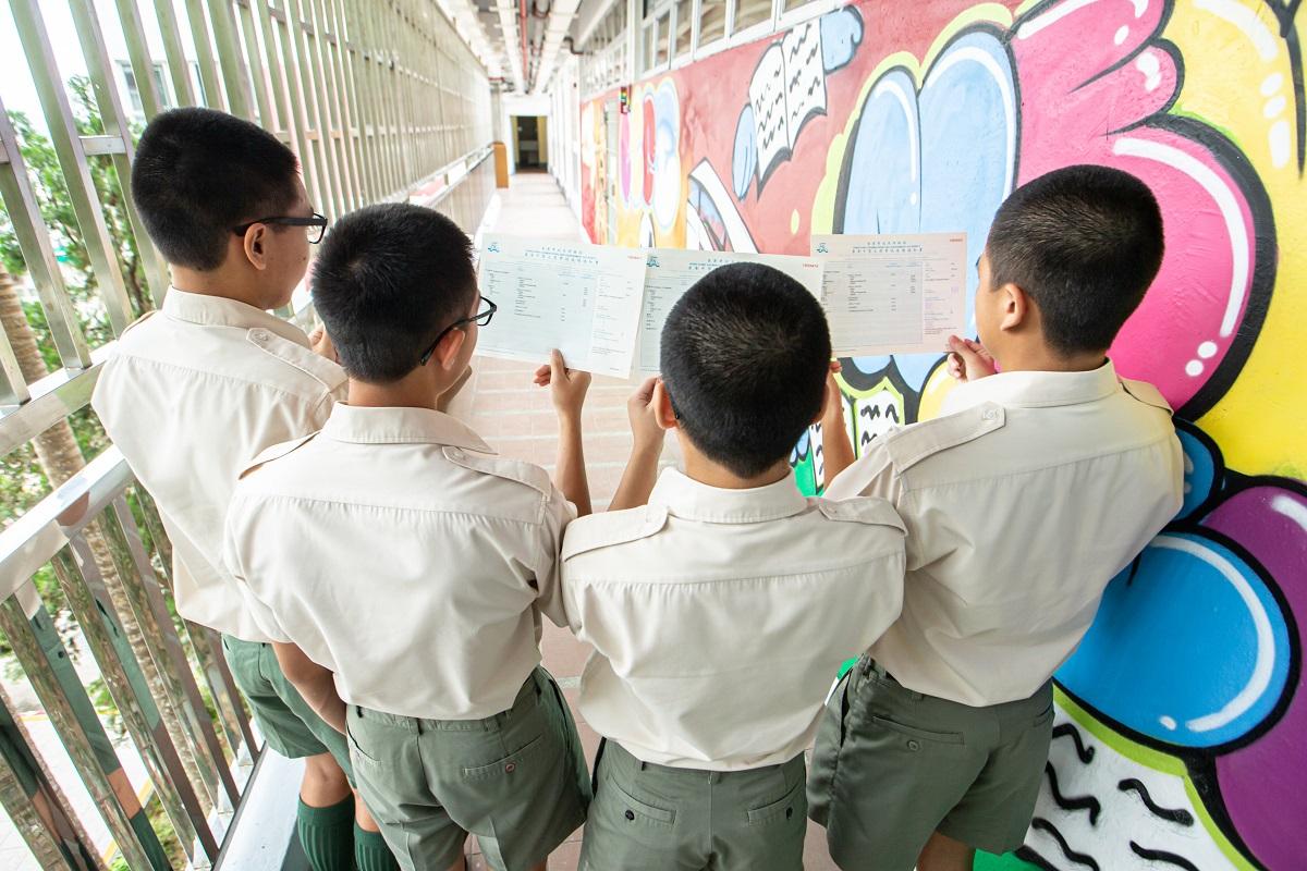 歌連臣角懲教所青少年在囚人士一起展示成績單,分享努力學習的成果。政府新聞處