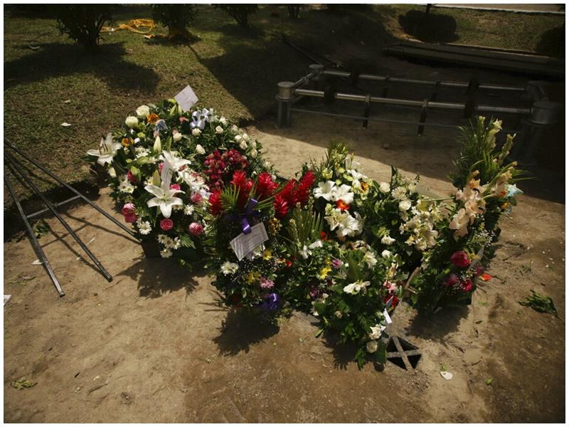 民眾在一對日前非法偷渡溺斃的父女墓上獻花。AP