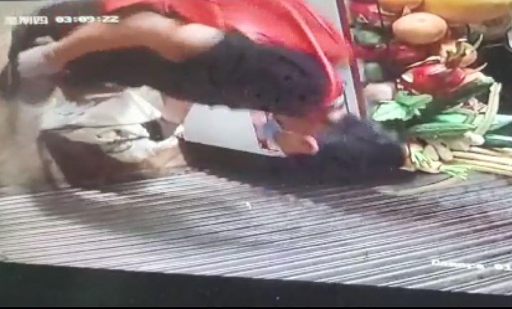 他揹上紅色手袋,並手持膠袋離開店舖。影片截圖
