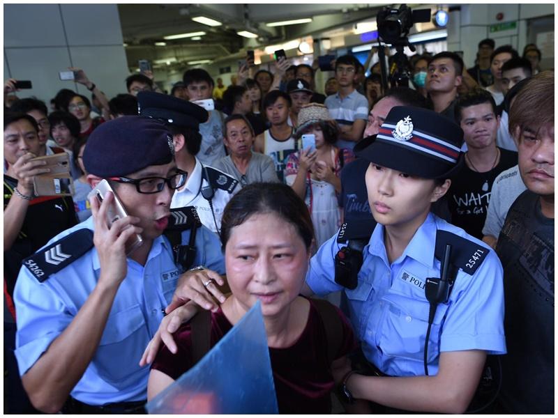中年女子在警方護送下上警車。