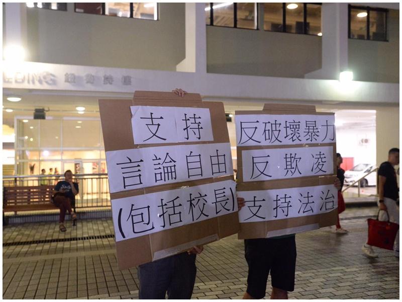 2名中年男子手持支持校長標語。