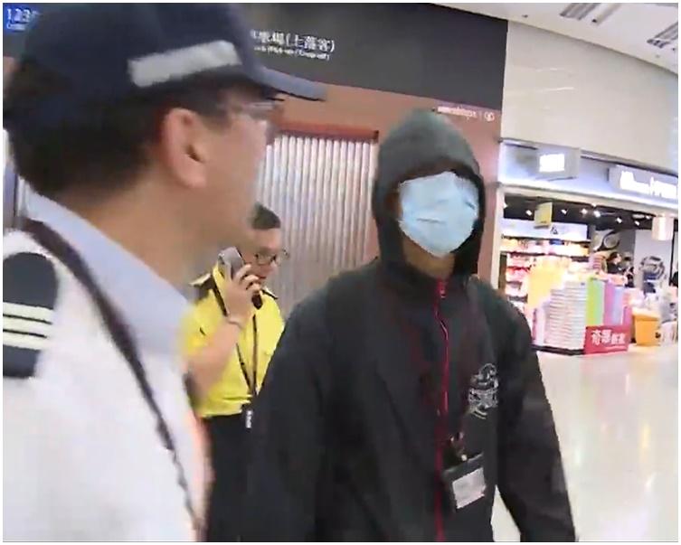 疑似港鐵員工(戴口罩)展示「香港撐住」海報後,被保安帶走。資料圖片