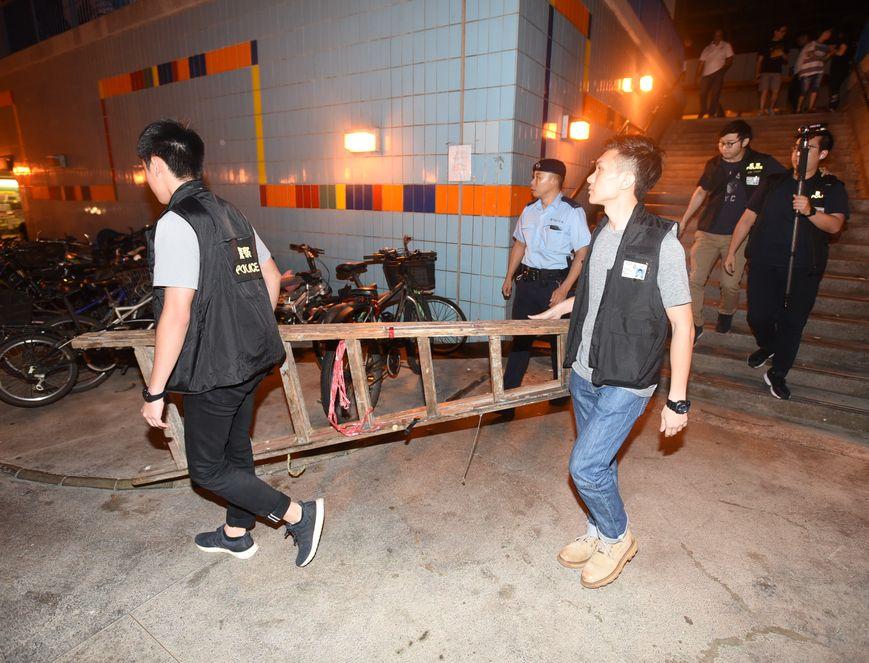 警員在清拆大埔墟車站行人隧道的巨型海報時,使用舊式A字梯。