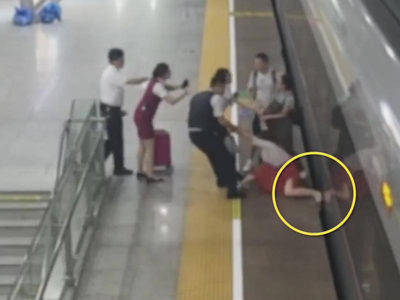 女子將腳插入月台和列車之間的空隙,企圖延止列車開出,被工作人員拉走。(網圖)