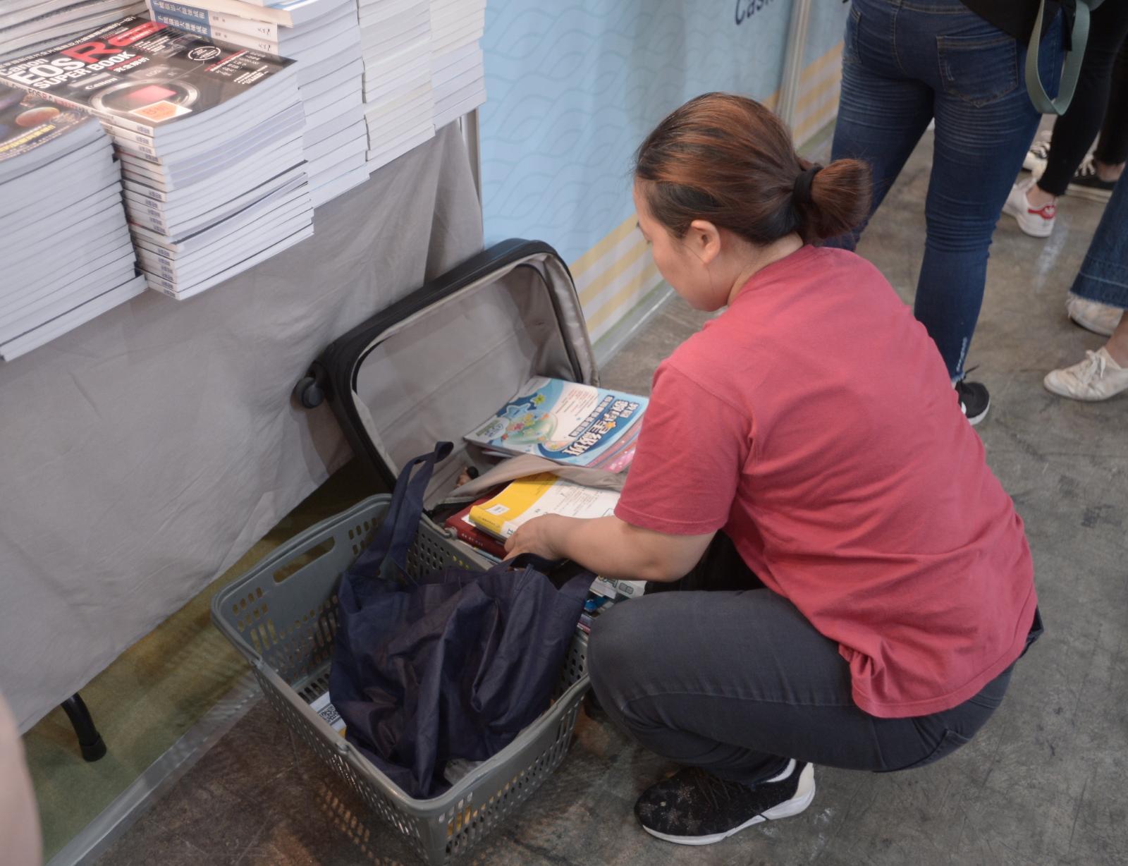 市民買得心頭書,將書放入行李箱。