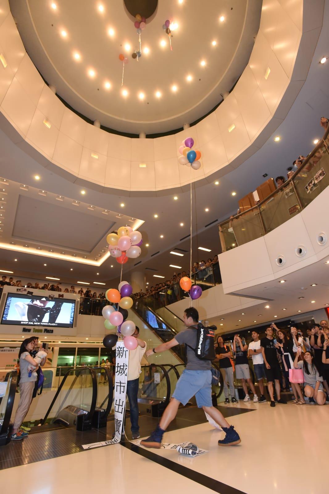有人將貼有抗議標語的氣球在商場內升空。