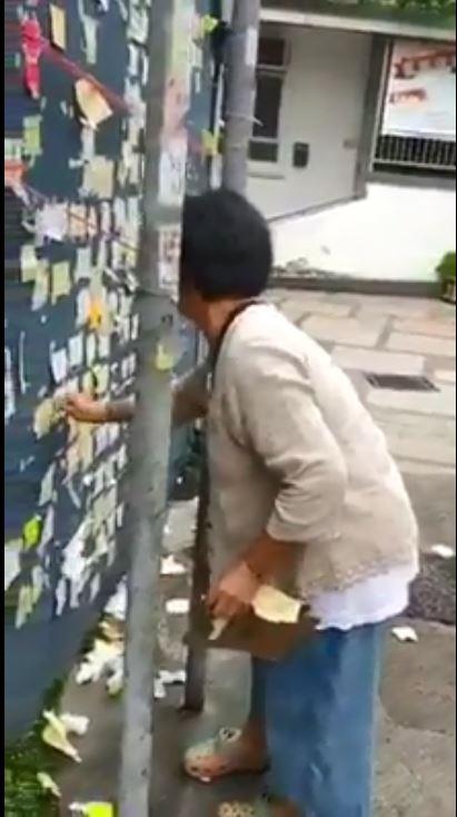 一名中年女子正撕走貼在牆上的紙張。影片截圖