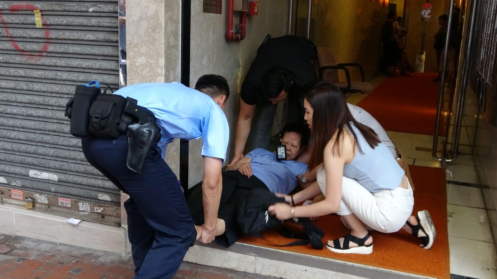 老婦途經現場時感不適,坐於大廈地下休息期間暈倒。