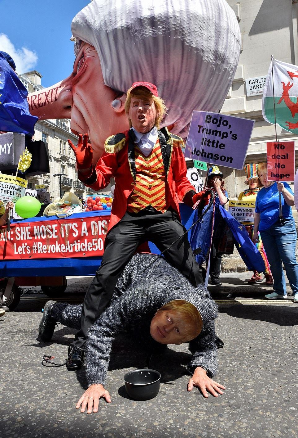 有人打扮成小丑和狗,諷刺約翰遜奉承美國總統特朗普。 網圖