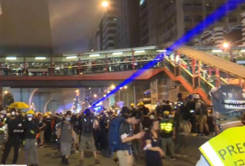有示威者向警察方向照射強烈紫色光束。有綫新聞
