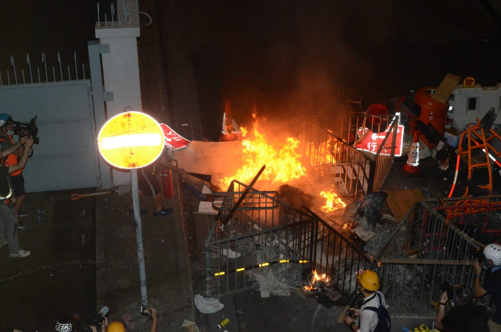 有記者取喉將示威者縱火焚燒的雜物救熄