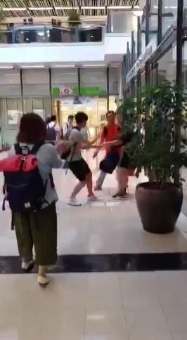 男子一邊拉扯一邊逃入圖書館。影片截圖