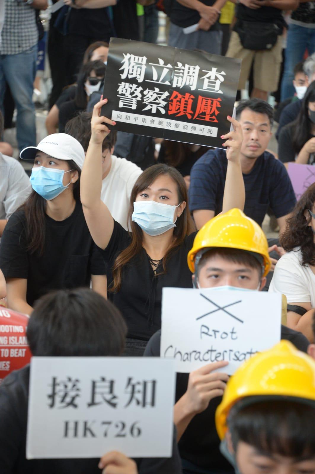 集會人士在場舉起標語靜坐。