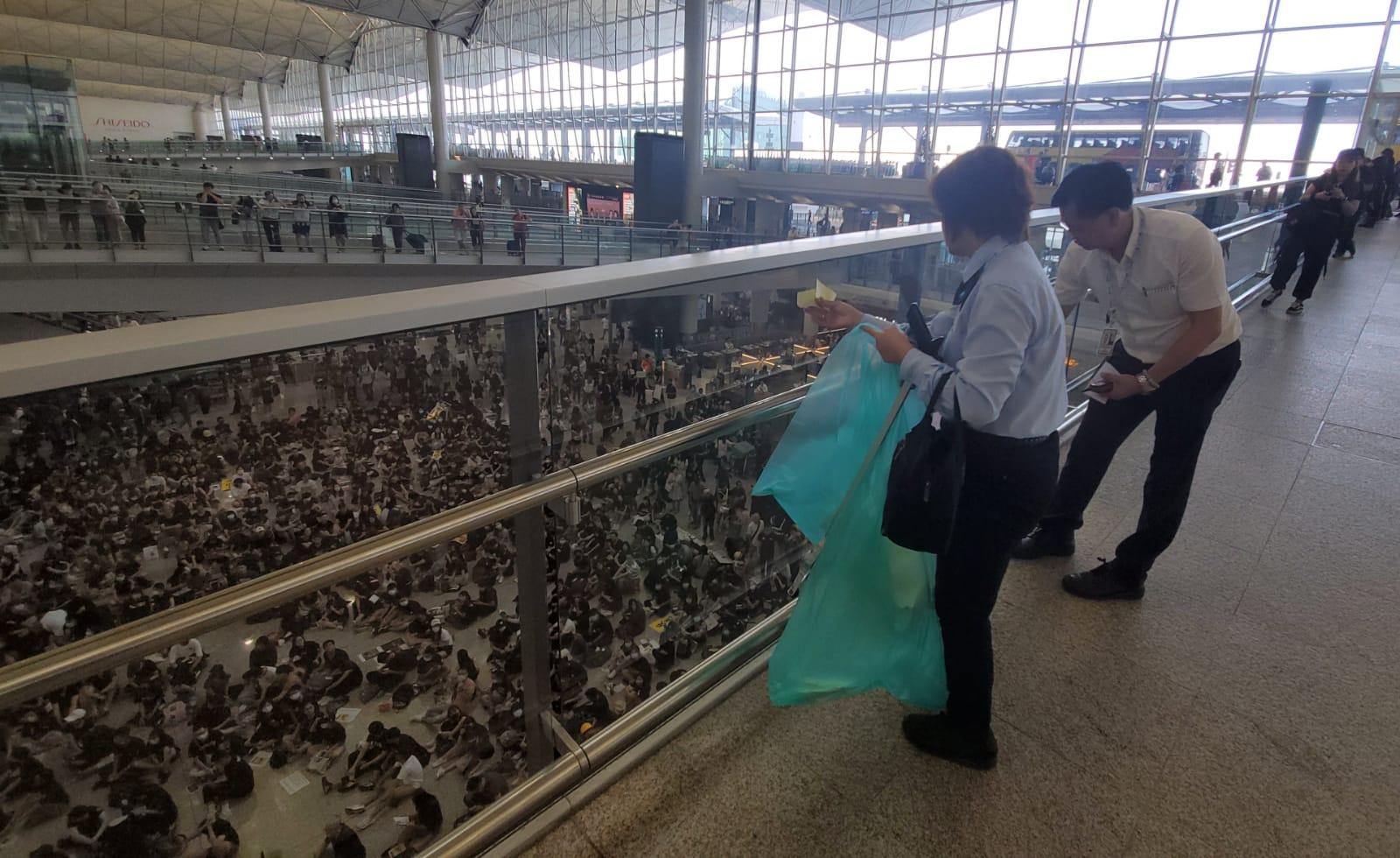 機場職員清理通往離境大堂通道上的標貼時,遭集會人士喝倒彩。