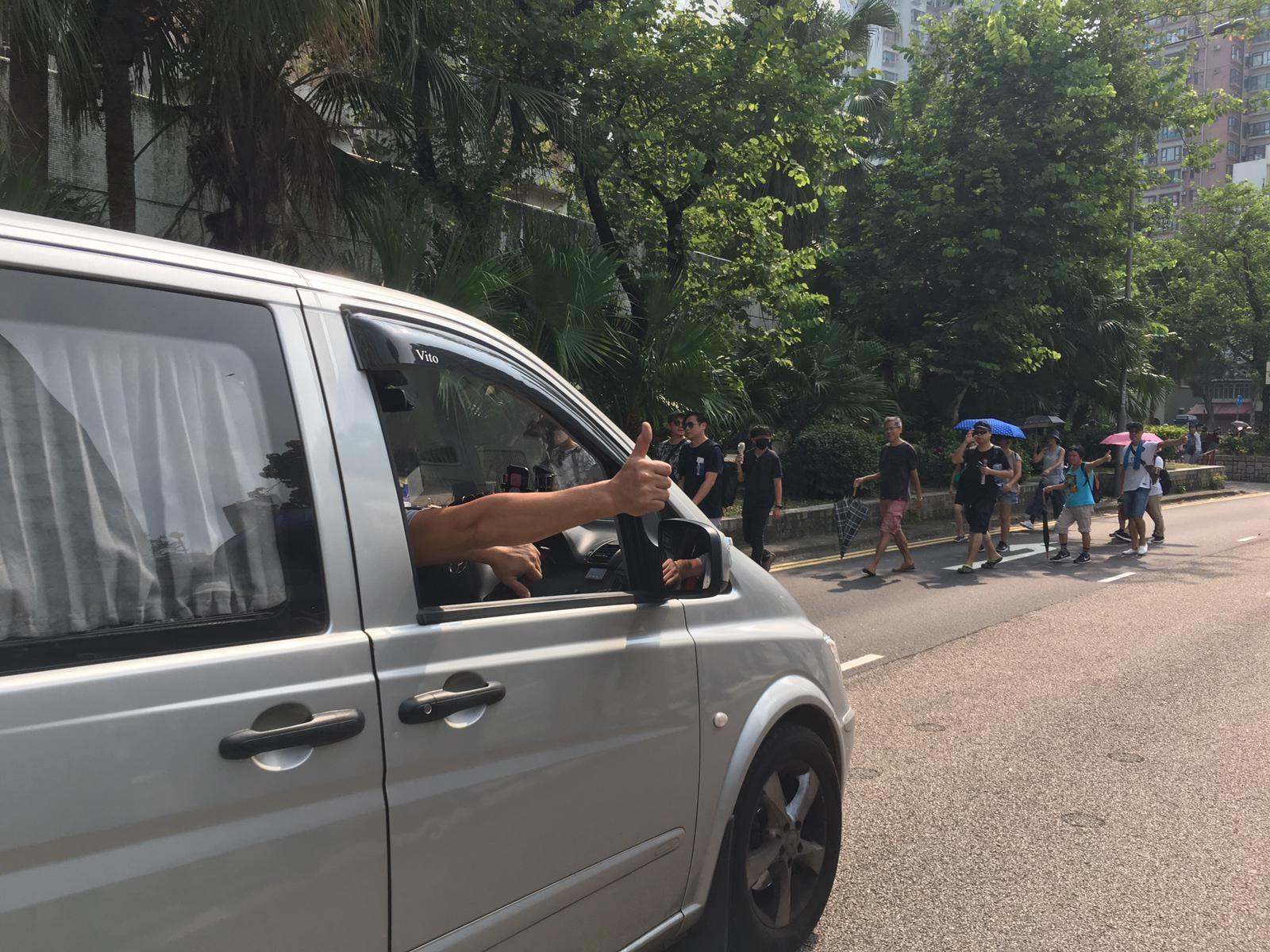 有司機駛過遊行隊伍時舉起姆指,遊行人士拍掌回應。