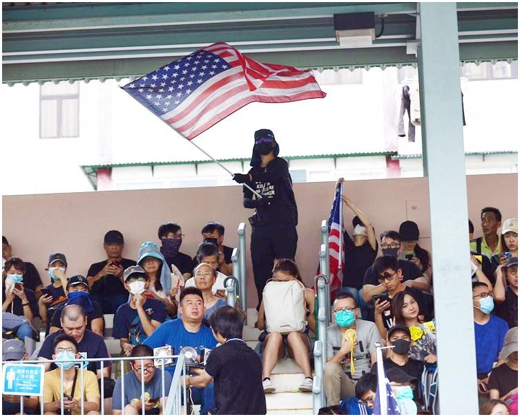 楓樹街遊樂場人高舉美國國旗。