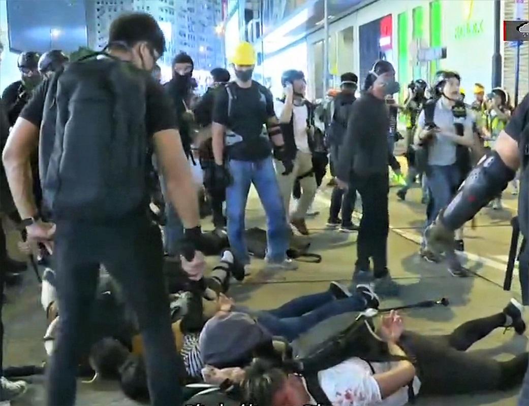 有疑為警員的黑衣人持警棍拘捕示威者。
