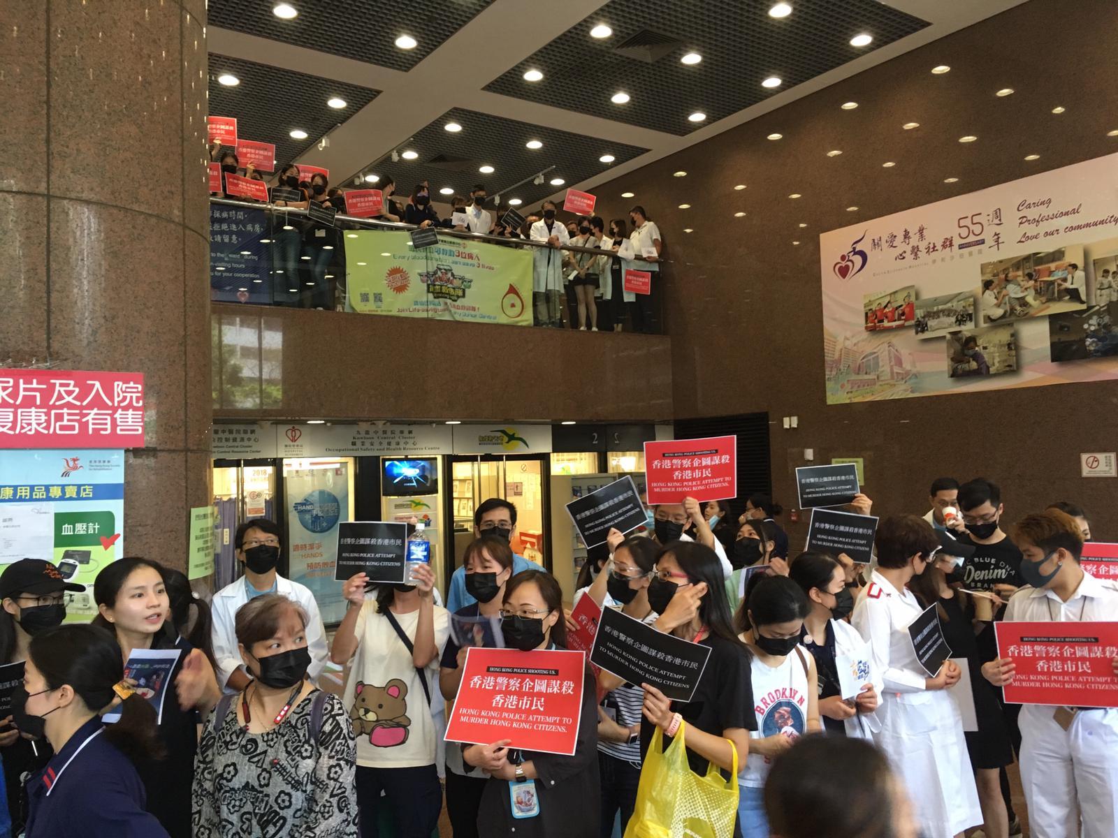 他們手持「香港警察企圖謀殺香港市民」標語。
